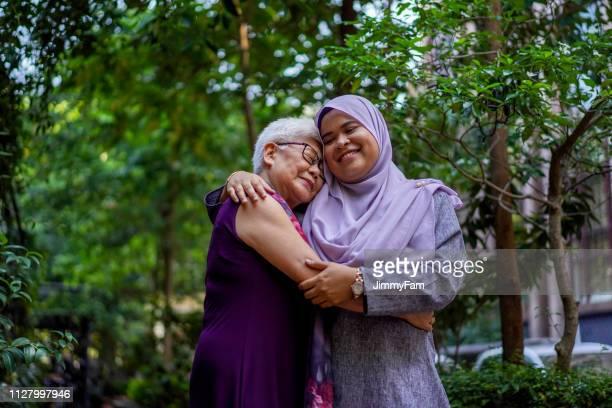 een knuffel zegt het al, multiraciale saamhorigheid en kracht - zuidoost aziatische etniciteit stockfoto's en -beelden
