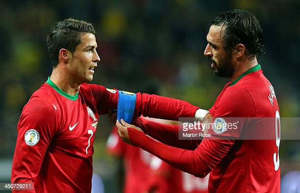Huga Almeida helps Cristiano Ronaldo of Portugal with his captains bandage runs with the ball during the FIFA 2014 World Cup Qualifier Play-off...