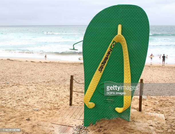 A huge advertising replica of a Havaianas 'flip flop' used at the beach side as a shower on Fistral Beach Newquay UK's centre of Surfing is around...