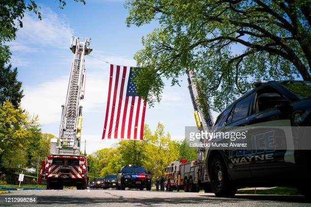 A huge American flag hangs over the procession during the funeral of Glen Ridge Police Officer Charles Roberts after he passed away from the...