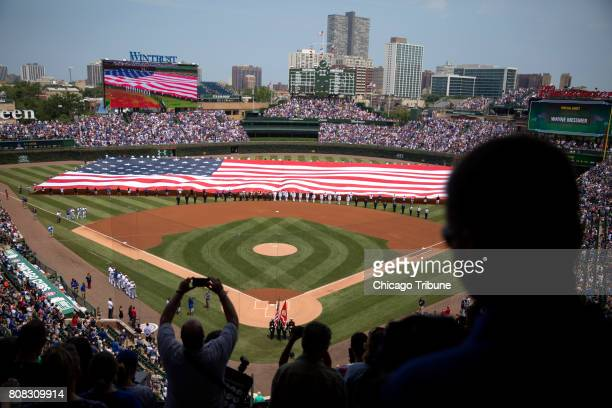 A huge American flag is unfurled before the Chicago Cubs versus Tampa Bay Rays game Tuesday July 4 at Wrigley Field in Chicago