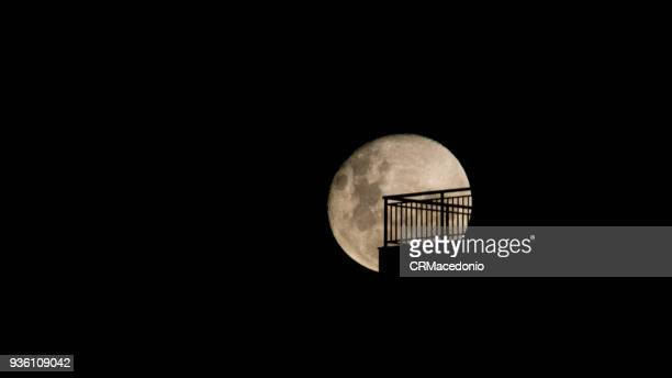 a huge  blood moon  on the home balcony. - crmacedonio stock photos and pictures