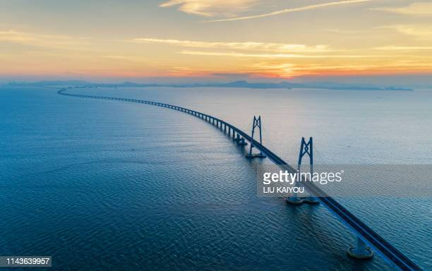 huge bridge with beautiful sunset hong kong-zhuhai-macau bridge - brücke stock-fotos und bilder