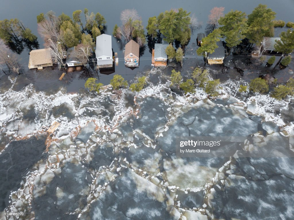 Huge chunks of ice propelled by wind and flood waters  threatens cottages on Grand Lake, New Brunswick, Canada : Stock Photo