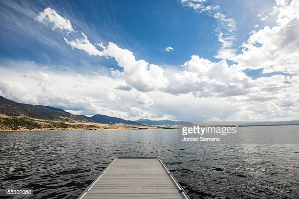 Huge clouds over a deserted lake and dock.
