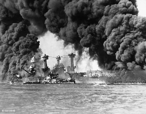 Huge columns of smoke go up from the USS West Virginia and the USS Tennessee crippled in their berths at Pearl Harbor Hawaii by a Japanese surprise...