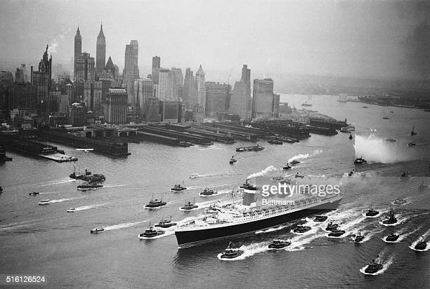 A huge cordon of tugs accompanies the new superliner United States past the New York skyline June 23 as the 73 million dollar passenger ship...