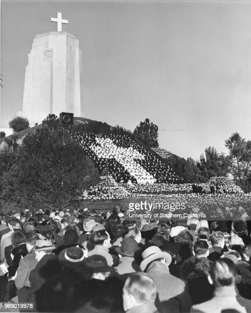A huge cross stands in the background of a crowd of thousands during the Easter Sunrise Services at the Forest Lawn Memorial Park Glendale California...
