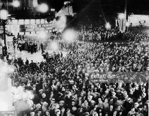 Huge crowd gathers outside the Warner Brothers theater on Wiltshire Boulevard in Los Angeles for a film premiere, 1930s. The marquee reads in part...