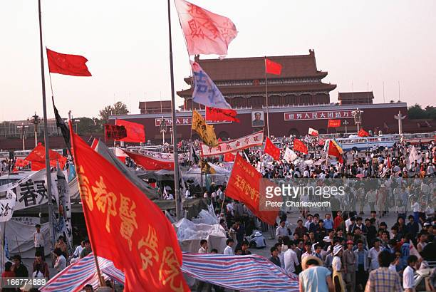 A huge crowd of flag waving prodemocracy demonstrators protest in Tiananmen Square in front of the Forbidden City and its portrait of Mao Tse Tung...