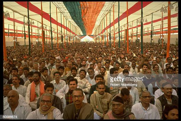 Huge crowd of Hindu nationalist Bharatiya Janata supporters attending BJP convention sitting in party colorsroofed tent