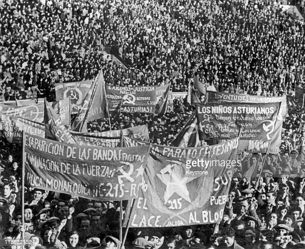 A huge crowd of people carrying banners and flags at a communist demonstration attended by 40 in the Monumental Bullring in Madrid Spain 3 March 1936