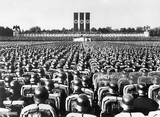 A huge crowd of soldiers in combat gear stands at attention beneath the reviewing stand at Nuremberg Germany listening to a speech by the German...