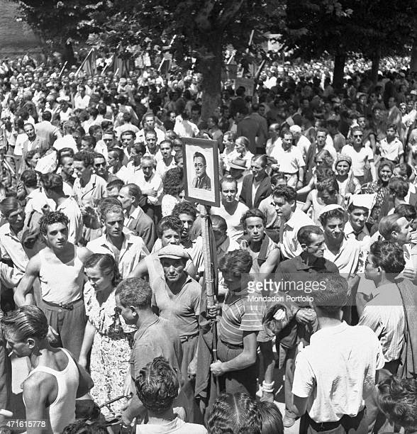 A huge crowd protesting after Italian politician and General Secretary of Italian Communist Party Palmiro Togliatti was shot A man carrying with him...