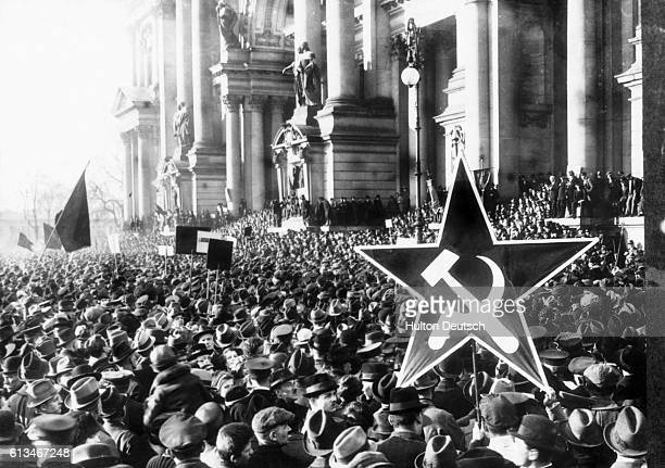 A huge crowd turns out for a Communist rally in Berlin One person holds a large starshaped placard emblazoned with a hammer and sickle 1918