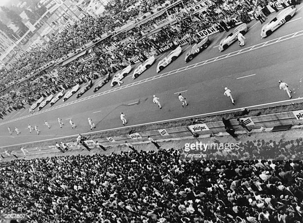 A huge crowd watch as drivers run to their cars at the start of the 1969 Le Mans 24Hour Race