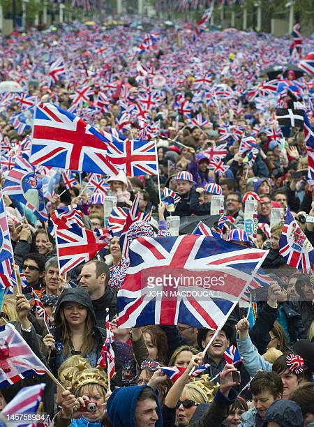 Huge crowds cheering with Britain's Union flags march down the Mall towards Buckingham Palace to celebrate the Queen's Diamond Jubilee in London on...