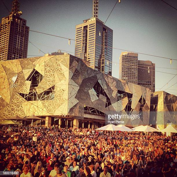 Huge crowds gather at Federation Square to watch the third round match between Bernard Tomic of Australia and Roger Federer of Switzerland during day...