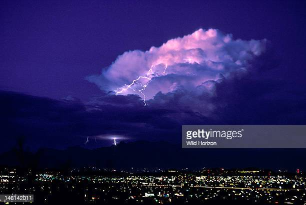 Huge cumulonimbus cloud illuminated at twilight by pink alpenglow hues plus intracloud lightning Tucson Arizona USA