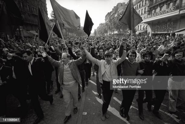 A huge demonstration of students and workers on the streets of Paris under red and black flags after two weeks of general strike and occupation of...