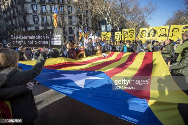A huge flag seen laying a head of the demonstrators with portraits of political prisoners during the protest ANC and Òmnium Cultural together with...