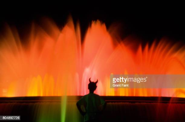 huge fountain at night. - devil costume stock photos and pictures