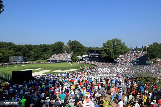 Huge galleries watch the group of Tiger Woods Justin Thomas and Rory McIlroy as they complete their round on the 18th green during the completion of...