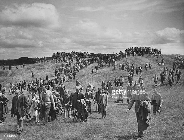 A huge 'gallery' of spectators follows English golfer Henry Cotton across the Royal Liverpool Golf Club in Hoylake during the British Open 5th July...