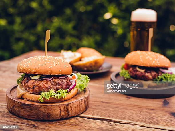 Huge gourmet cheese burgers on a rustic wooden table outdoors