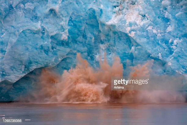 Huge ice chunk breaking from the edge of the Kongsbreen glacier calving into Kongsfjorden, Svalbard / Spitsbergen, Norway.