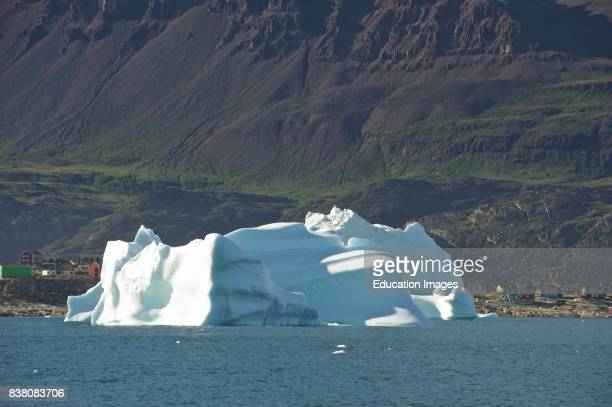 Huge iceberg floats in the Disko bay, in front of Qeqertarsuaq -the biggest town on the Disko island in Western Greenland.
