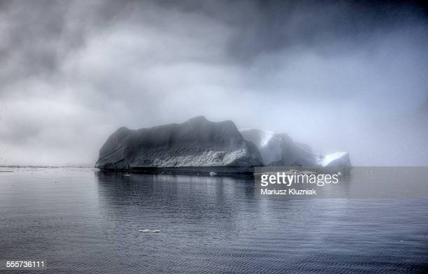 Huge iceberg, fog and clouds around