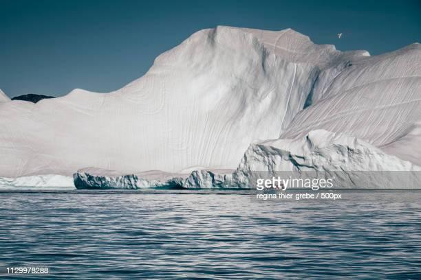 huge iceberg - small boat - ilulissat stock-fotos und bilder
