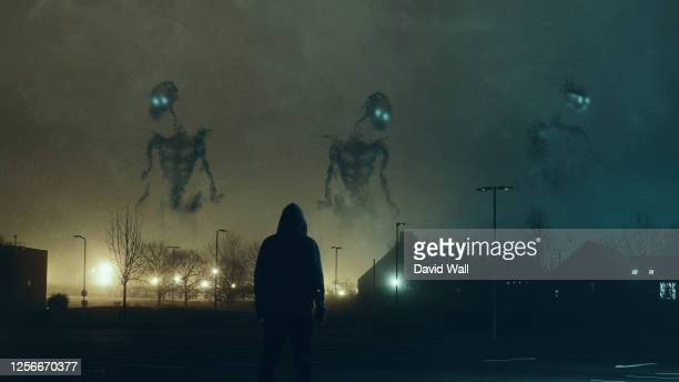 huge monster skeletons appearing above a city on a foggy winters night. with a lone figure looking up. with an old grunge, textured edit. - emotion stock pictures, royalty-free photos & images