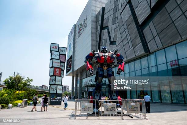 A huge Optimus Prime stands on a plaza in front of a shopping mall 'Transformers 5 the last knight' directed by Michael Bay and starred by Mark...
