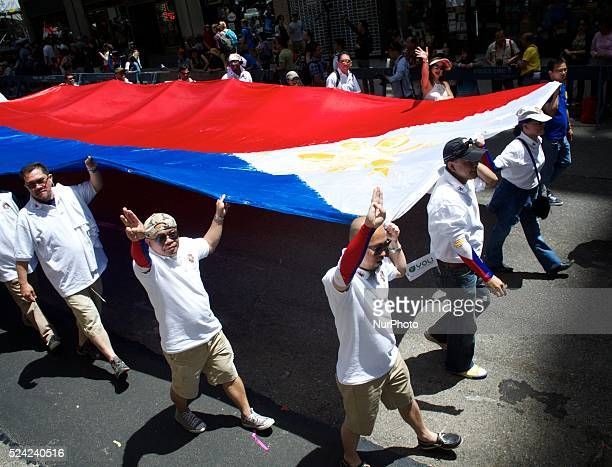 A huge Philippine flag is carried by members of a nonprofit organization in the parade at the 116th anniversary celebration of Philippine...