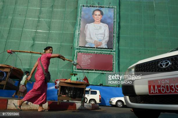 TOPSHOT A huge portrait of Myanmar's de facto leader Aung San Suu Kyi is displayed on a building construction site overlooking Mahabandoola park in...