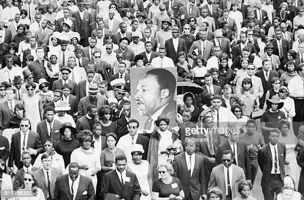 A huge portrait of slain civil rights leader Dr Martin Luther King is held up by marchers during his funeral procession here April 9th More than...