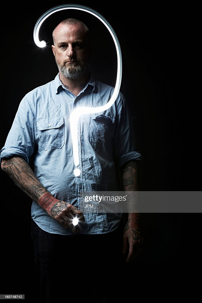Huge question mark in front of man : Stock Photo