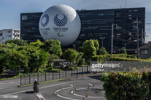 Huge semi-sphere displaying the Tokyo Olympics and Paralympics logos is displayed from the side of a driving school building on May 6, 2021 in Tokyo,...