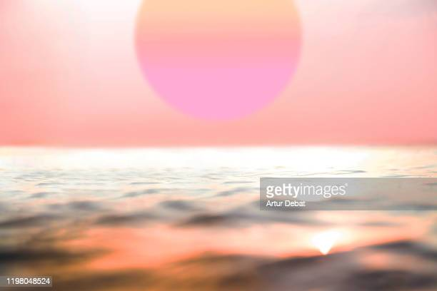 huge sun during beautiful pink sunset with the sea in bali. - spirituality stock pictures, royalty-free photos & images