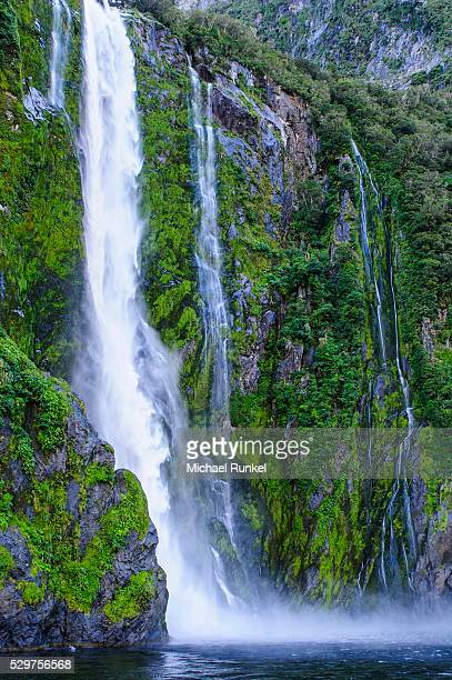 huge waterfall in milford sound, fiordland national park, unesco world heritage site, south island, new zealand, pacific - international landmark stock pictures, royalty-free photos & images