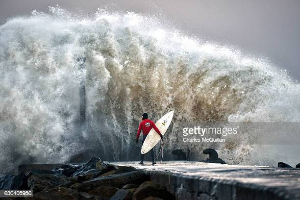 Huge wave crashes against Castlerock pier as professional surfer Al Mennie waits on a break in the swell on December 22, 2016 in Coleraine, Northern...