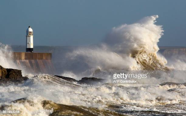 Huge waves strike the harbour wall and lighthouse at Porthcawl South Wales on October 16 2017 as Storm Ophelia hits the UK and Ireland Ireland was...