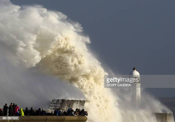 TOPSHOT Huge waves strike the harbour wall and lighthouse at Porthcawl south Wales on October 16 2017 as Storm Ophelia hits the UK and Ireland...
