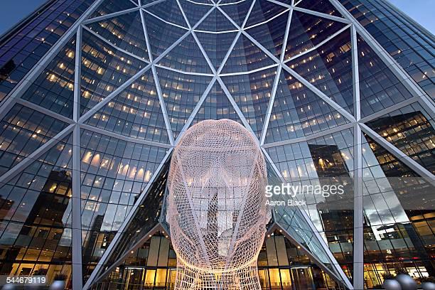Huge wire mesh head lit up in front of skyscraper