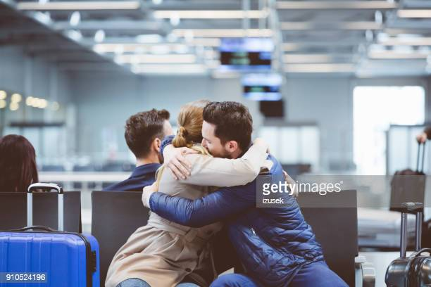 hugging couple in international airport - separation stock photos and pictures