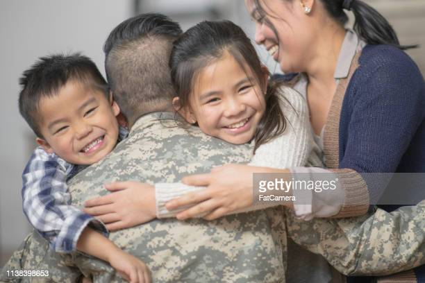 hugging family - army soldier stock pictures, royalty-free photos & images