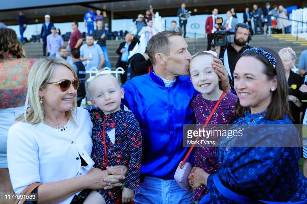 Hugh Bowman cuddles daughters Paige and Bambi with wife Christine and friend Jenny Moses after winning the Golden Rose on Bivouac during the Golden...