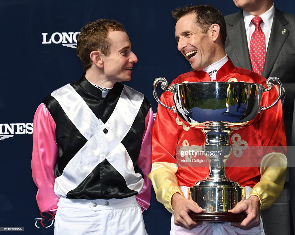 Hugh Bowman of Australia poses with the winning trophy and smiles at runner up Ryan Moore of the U.K during Longines International Jockeys' Championship at Happy Valley Racecourse on December 7, 2016 in Hong Kong, Hong Kong.